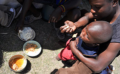 A child is fed in the South African refugee camp De Dooms. Photo by Courtney Brooks via flickr.com.