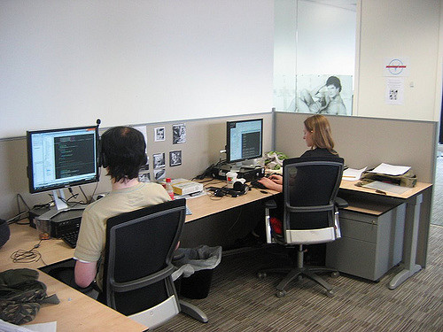 Photo of two people in a cubicle working on computers.