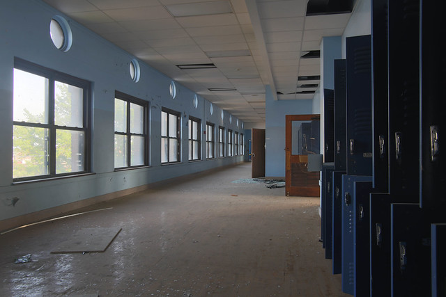Photo of an empty school hallway with lockers open.
