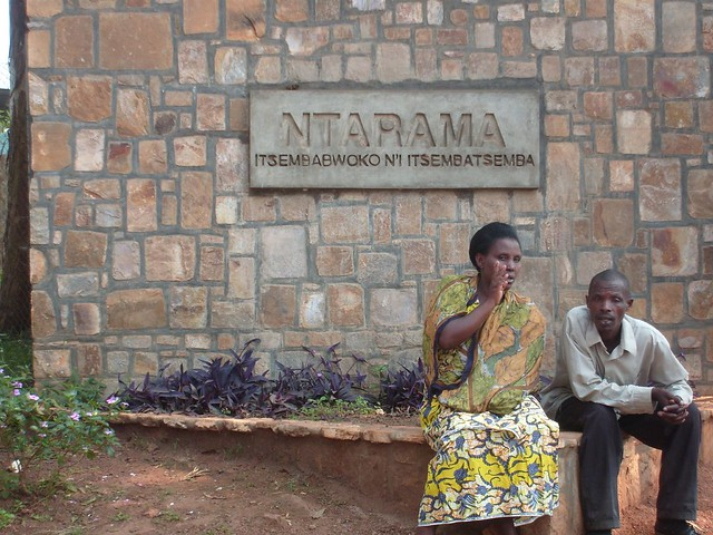 A Rwandan woman and man sit on a bench outside of Ntarama and wait for gacaca court to begin.