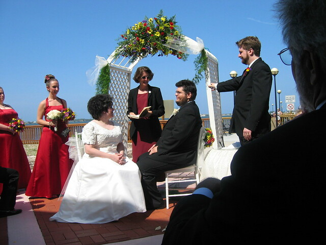 Photo shows a bride and a groom sitting on chairs in front of a woman officiating.