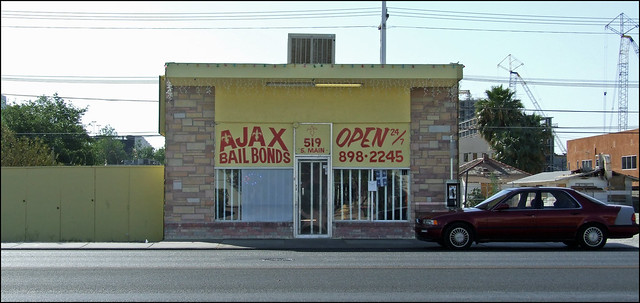 "Photo of a building with a sign that says, ""Ajax Bail Bonds, Open 24/7"""