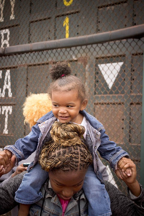 Photo of a black woman holding a black child on her shoulders.