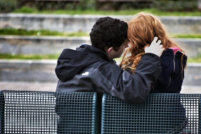 Photo of a romantic couple's backs as they sit on a bench. One has a hand in the other's hair.