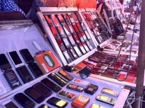 A cell phone vendor shows their wares at the Kumasi Central Market