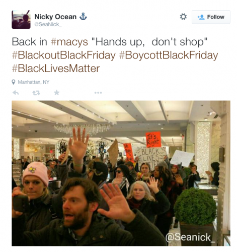 "A tweeted picture of predominantly white faces with their hands up in a mall. Tweet reads: Back in #macys ""hands up, don't shop"" #blackoutblackFriday #boycottblackfriday #blacklivesmatter. tweet by @seanick_"