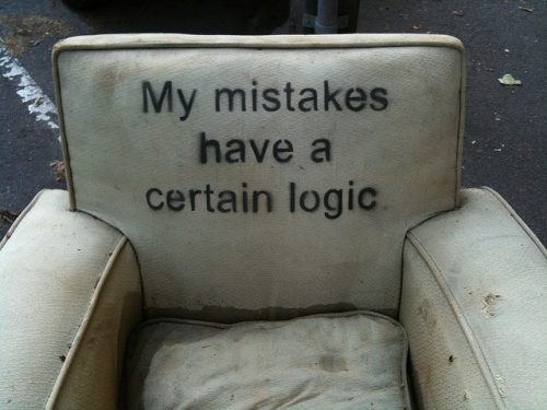 "A dirty old chair with the words ""My mistakes have a certain logic"" stenciled onto the back."