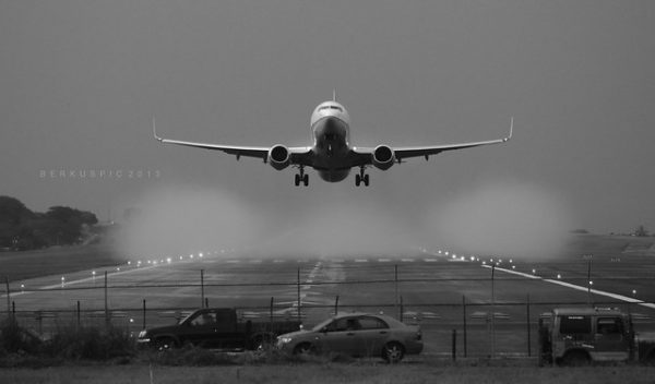 Black and white photo of a large commercial plane just above the ground as if it is landing or taking off.