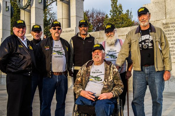 A group of seven vietnam veterans, wearing vietnam t-shirts. one is in a wheelchair, the others stand around him.