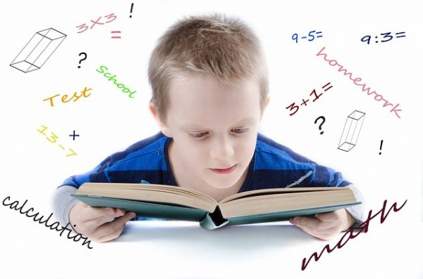"a boy looks at a book. around his head are math problems and works like ""homework,"" and ""calculation"""
