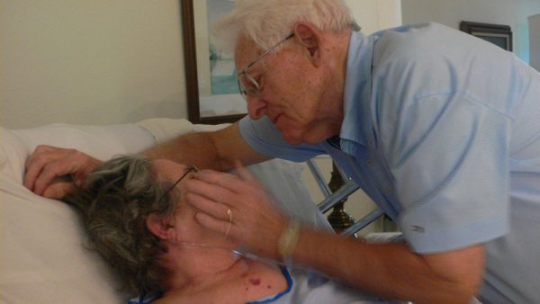 Photo of a man touching his wife's face while she lays in a hospital bed.