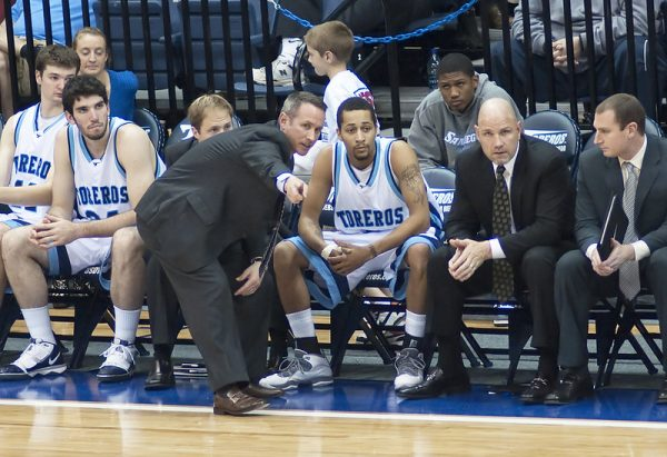 Photo shows college basketball players sitting on a bench while a coach crouches next to them. The players are wearing white jerseys with blue letter that says Toreros.