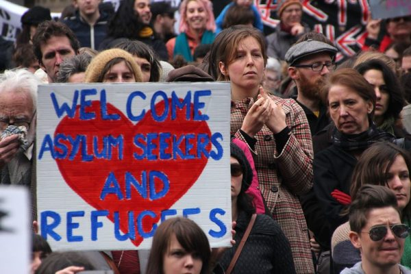 """Photo shows a protester holding a sign that reads, """"welcome asylum seekers and refugees,"""" over top of a red heart."""
