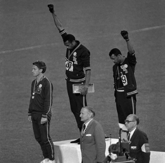 U.S. athletes Tommie Smith, center, and John Carlos stare downward during the playing of the Star Spangled Banner after Smith received the gold and Carlos the bronze for the 200 meter run at the Summer Olympic Games in Mexico City on Oct. 16, 1968
