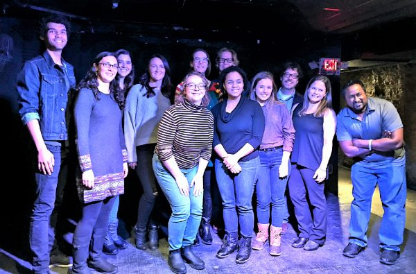Photo of twelve people lined up on a stage for a photo. Everyone is smiling. The venue is dark and you can see an exit sign behind everyone's heads.