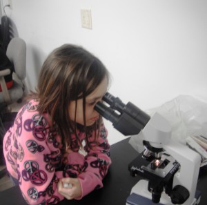 Girl looking into a microscope by VFW National Home for Children via Flickr.