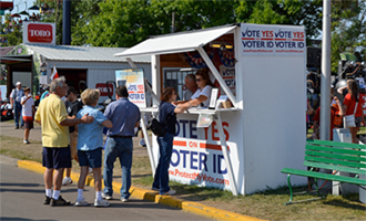 A booth at the Minnesota State Fair urged voters to pass a ballot initiative requiring government-issued ID to cast a ballot. The measure did not pass. Image via Flickr CC.