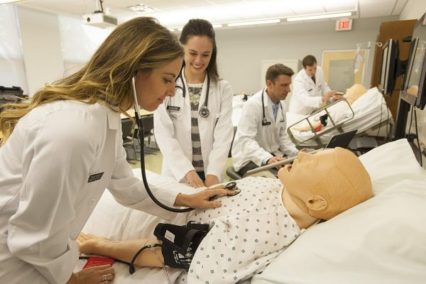 A student uses a stethoscope to listen to the heart of a dummy