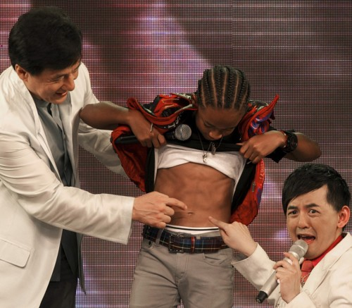 In it, 11-year-old Jaden has lifted his shirt to show off his abs, while  co-star Jackie Chan and a man I presume is the event host marvel at them: