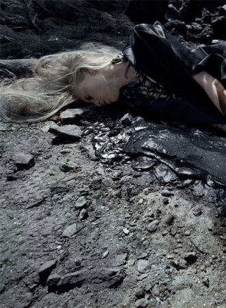 torso, head, and hair of a blonde woman, lying dead-looking in an oil puddle on the edge of a beach