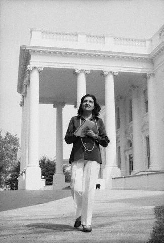 Helen Thomas Standing in Front of White House with Note Pad