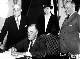 FDR signs the Wagner Act into law. Deciding against various corporate challengers, the Supreme Court upheld the act in 1937.