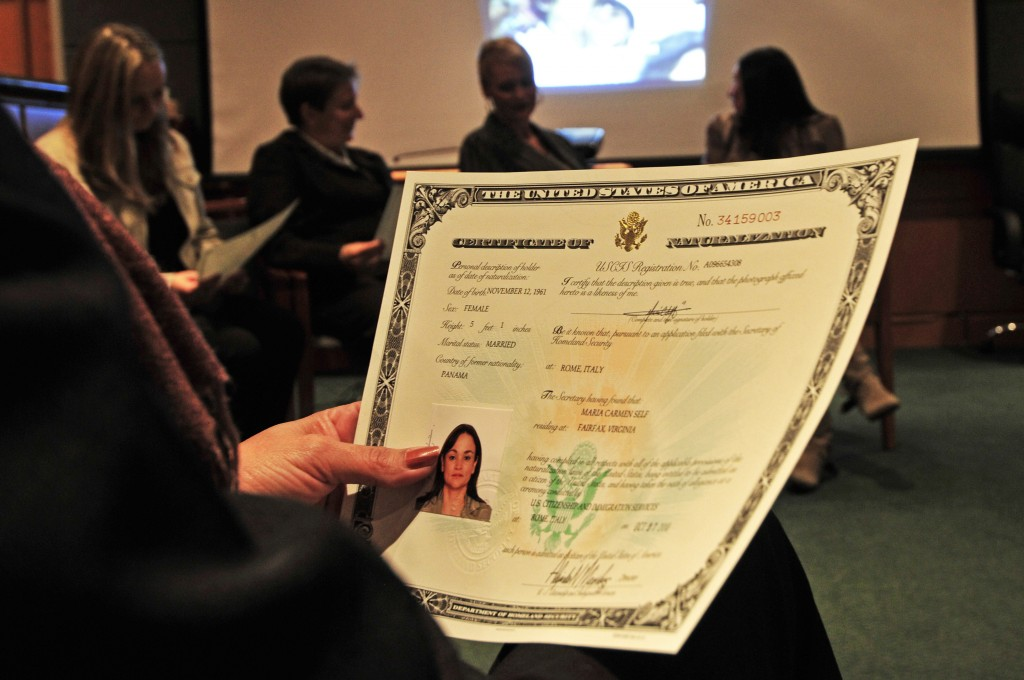 A newly naturalized citizen displays her certificate. U.S. Navy photo.