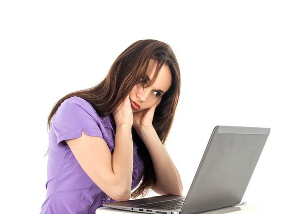 A stressed-out woman holds her head and looks at her computer.