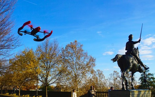 Photo of a drone flying in the air near a statue of Joan of Arc.