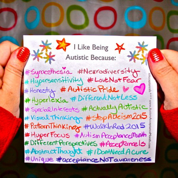 "Photo of two hands holding a paper that says ""I Like Being Autistic Because"""