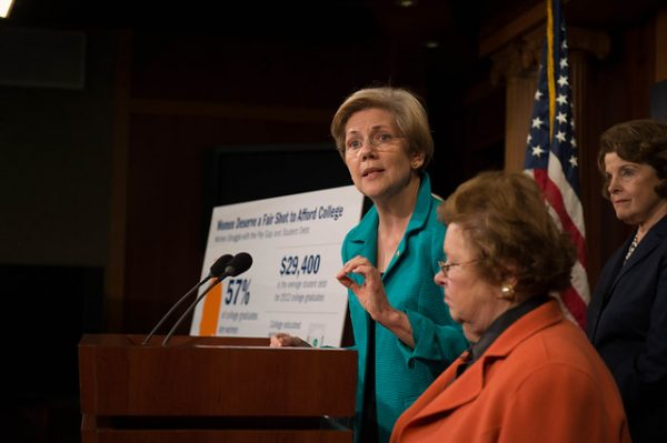 Photo of Elizabeth Warren speaking at a podium. There is a large sign next to her about how students afford college.