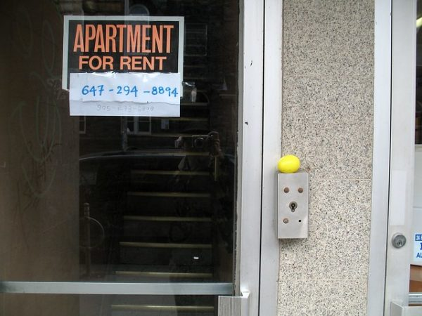 "Photo of a sign that read ""Apartment for Rent"" on a glass door. You can see stairs through the door and there is a phone number written below the sign."