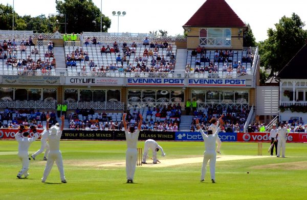 Photo of cricket players in white uniforms holding their arms in the air to signal for an appeal