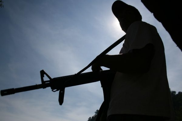 Photo of a silhouette of a person holding a rifle.
