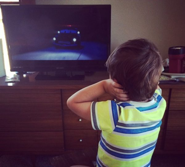 Photo is shows a child covering their ears while watching tv