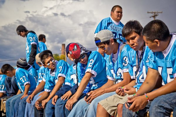Photo of ten boys sitting together all wearing matching blue football jerseys. Some have blue face paint under their eyes.