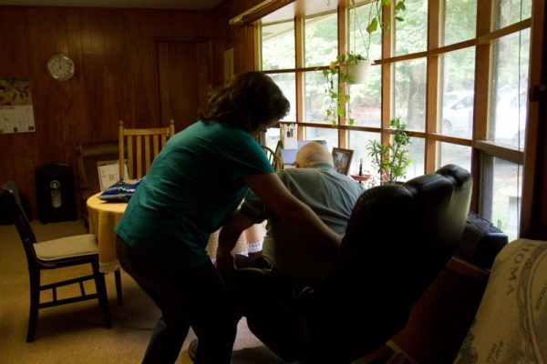 A woman helps an elderly man get up from his chair